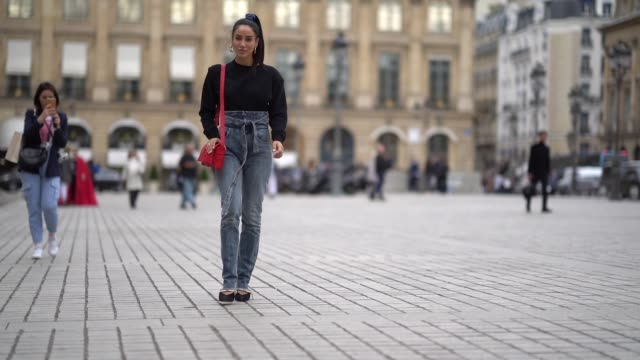 tamara kalinic wears louis vuitton earrings a black sweater with shoulder pads a red bag washedout blue denim highwaist ripped hem pants with an... - shoulder bag stock videos & royalty-free footage