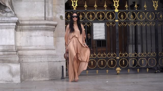 tamara kalinic wears sunglasses, bracelets, a lustrous light brown pleated high-low dress, a brown stella mccartney handbag, brown heeled mules,... - fashion week stock videos & royalty-free footage