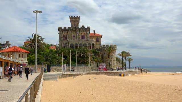 tamariz beach with estoril castle in the background, estoril, near lisbon, portugal - エストリル点の映像素材/bロール
