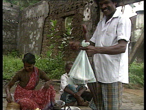 concerns about costs of war and distribution of aid sri lanka vavuniya ext ms clock at end of street pull out people along on foot and on bicycle in... - bean bag stock videos & royalty-free footage