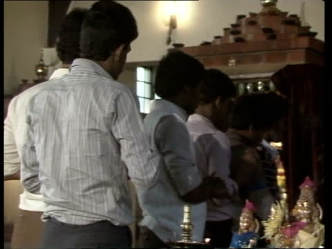 a england south london hindu temple hindu priest praying at shrine pull out tamils at service cbv tamils praying as priest offers blessing bv tamils... - 礼拝点の映像素材/bロール