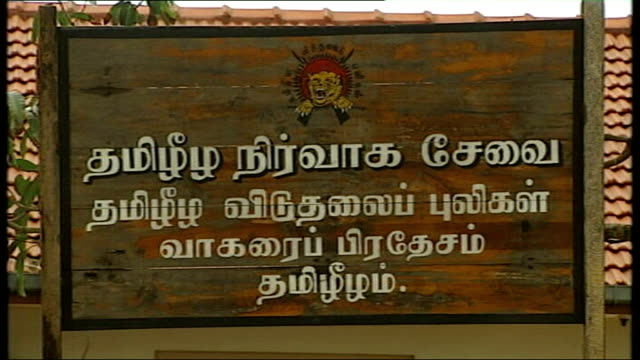 tamil tigers on retreat government soldiers in refugee camp sign outside building that used to be tamil tigers headquarters building reporter talking... - sri lankan flag stock videos & royalty-free footage