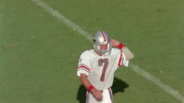 tampa bay bandits vs houston gamblers, football player walks off field (john reaves) looking disappointed, takes helmet off  - 1985 stock-videos und b-roll-filmmaterial