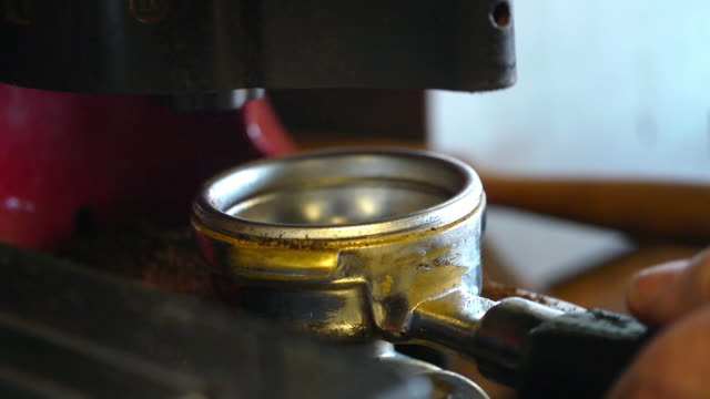 tamping espresso grounds in the portafilter / filter handle - 挽く点の映像素材/bロール