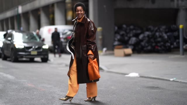 tamu mcpherson wears a brown leather shiny long coat, an orange knitted bag, orange flared pants, pointy shoes, outside cinq a sept, during new york... - brown stock videos & royalty-free footage