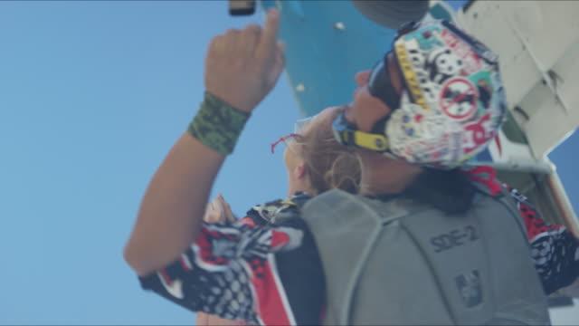 vídeos de stock, filmes e b-roll de tandem girl exiting airplane with instructor - paraquedismo