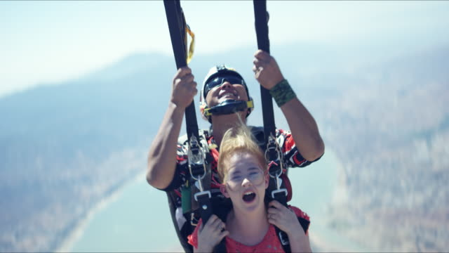tandem girl hangs on while parachute opens - parachuting stock videos & royalty-free footage