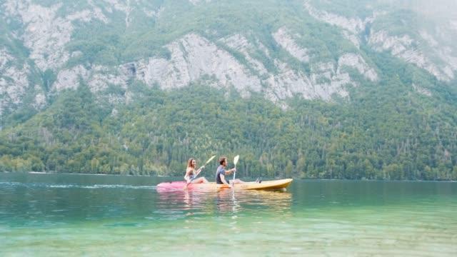 stockvideo's en b-roll-footage met tandem kajakkers peddelen in unison op lake bohinj in de zomer - julian alps