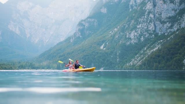 tandem kayakers paddling in unison on lake bohinj in summer - kayak stock videos & royalty-free footage