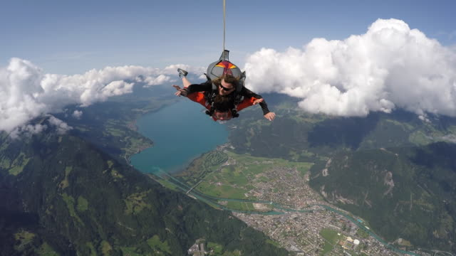 Tandem skydivers in free fall above alps