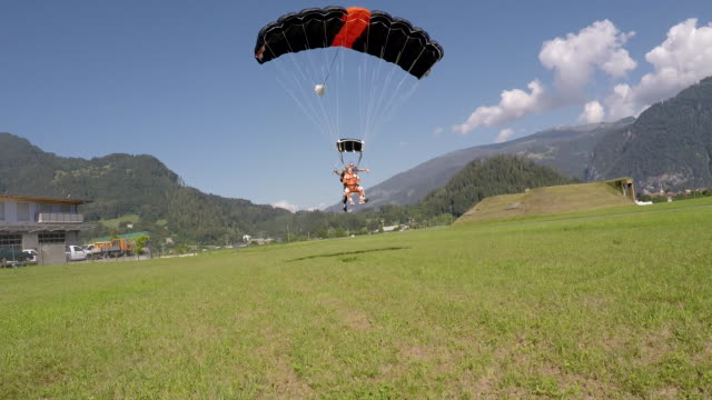 tandem skydivers landing on field - parachuting stock videos and b-roll footage