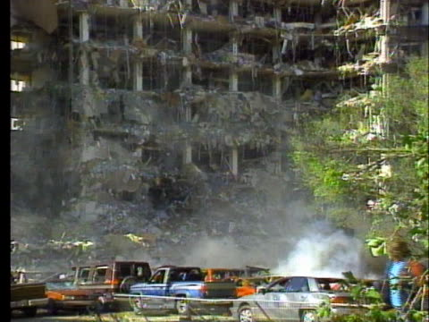 tangled mass of metal protrudes from the bombed murrah federal building as smoke still rises. - oklahoma city bombing stock videos & royalty-free footage