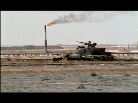 WS, ZI, MS, Tank abandoned in desert, burning oil well in background, Kuwait