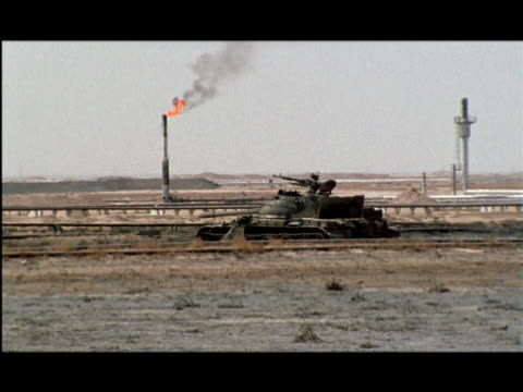 MS, ZO, WS, Tank abandoned in desert, burning oil well in background, Kuwait