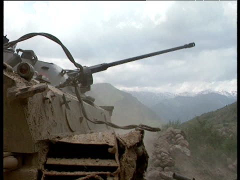 tank fires into mountainside and shells are ejected during tajikistan civil war 1992 - ムラがある点の映像素材/bロール