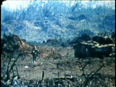 Tank firing soldiers advancing wounded soldiers being tended