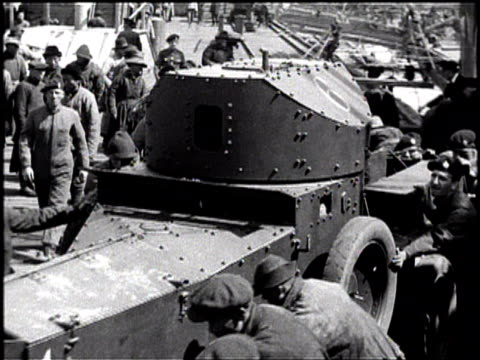 tank is lowered from a ship / the tank is guided down by soldiers / soldiers pull the tank along the dock / soldiers pull the tank to a building and... - guerra del pacifico video stock e b–roll