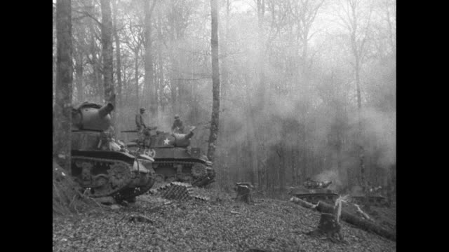 VS tank mortars fire in woods on the Western Front / CU officer speaks on field telephone / VS jeeps trucks approach and pass by as they move on road...