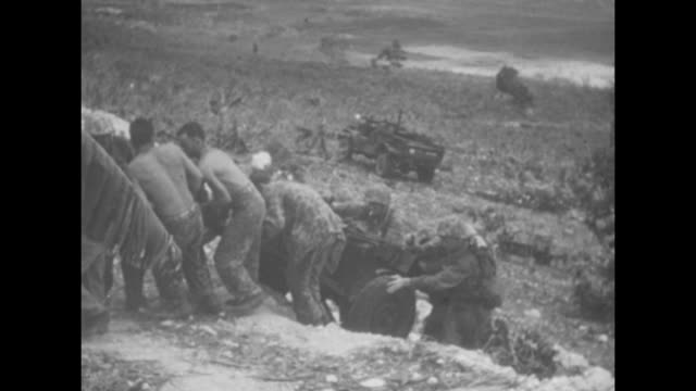 US tank moves ahead with US Marines walking behind it / Marine chasing duck in field / Marines advancing across field / line of Marines pulling...