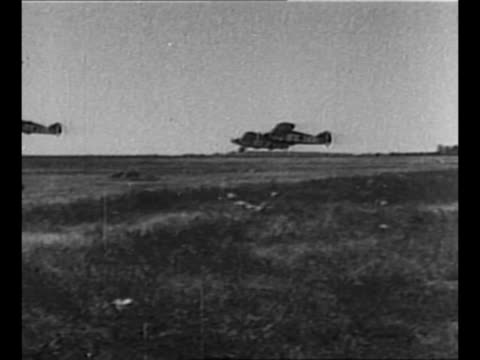 stockvideo's en b-roll-footage met tank moves away / italian soldiers load bomb into plane during ethiopian battle / cu soldier in gun turret of tank / italian bombers take off fly /... - 1930