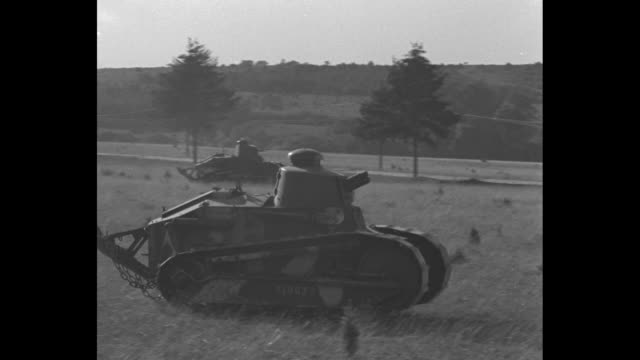 vidéos et rushes de ws tank moves in field with french soldiers following during french military maneuvers / ms tank moves across field / tank crosses small screen... - manoeuvre militaire