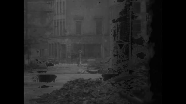 vídeos y material grabado en eventos de stock de us tank moving down street / smoke pouring from burning buildings / building collapsing into street / german soldier crossing street / us soldiers... - ataque con bomba