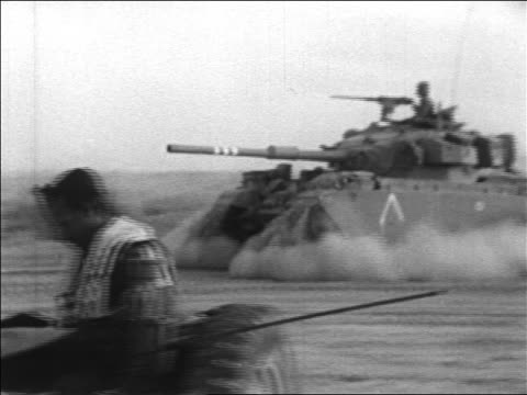 pan tank moving on desert / israeli soldier in yarmulke in foreground / six day war / newsreel - sechstagekrieg stock-videos und b-roll-filmmaterial
