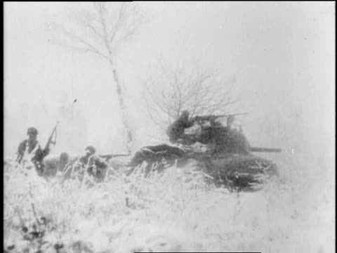 tank moving with soldier behind turret in winter conditions / soldier's face with other soldiers in background wading through snow / soldiers working... - 1944 stock videos & royalty-free footage