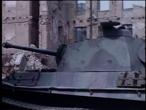tank standing in street, markings painted out, the rubble of destroyed buildings behind it / germany - rubble stock-videos und b-roll-filmmaterial