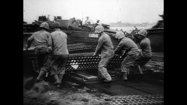 tank tracks truck wheels stuck in sand of iwo jima beach marines laying out metal mats vehicles moving on mats soldiers mobilizing - battle of iwo jima stock videos & royalty-free footage