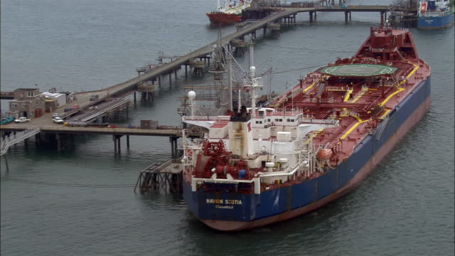 low aerial, tanker berthed on quay, milford haven, pembrokeshire, wales - pembrokeshire stock-videos und b-roll-filmmaterial