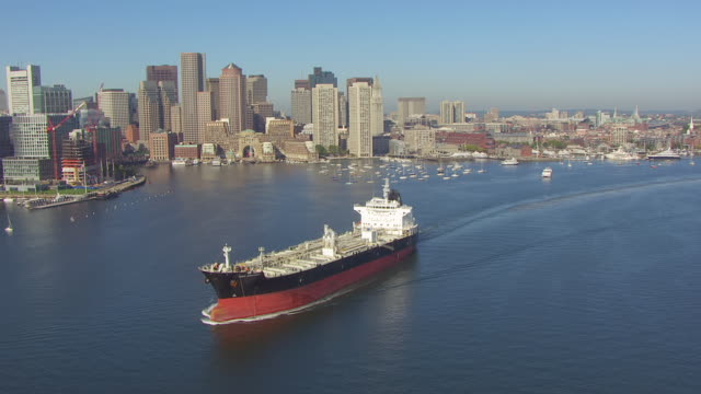 WS AERIAL POV Tanker ship moving on bay, financial district in background / Boston, Massachusetts, United States