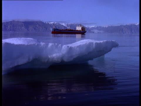 vídeos y material grabado en eventos de stock de a tanker travels near a small ocean iceberg.\n - buque tanque