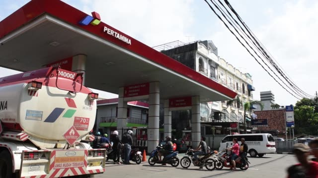 a tanker truck arrives at a pt pertamina gas station in jakarta indonesia on wednesday jan 21 motorcyclists wait in line in front of a tanker truck... - 軍用輸送車点の映像素材/bロール