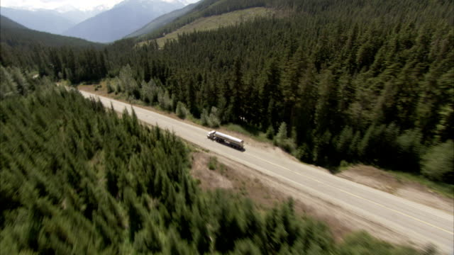 A tanker truck travels along a wooded mountain highway in Canada. Available in HD.