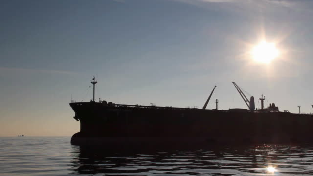 tankers silhouettes at sunset