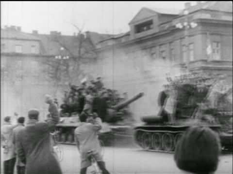 PAN 2 tanks carrying groups of civillians drive past camera / Hungarian uprising