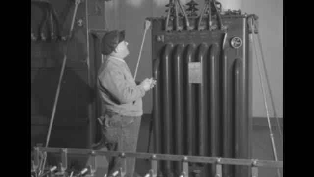 tanks filled with helium for barrage balloon being lowered into hold of ship / pan across equipment in room on ship to man standing in room... - helium stock videos & royalty-free footage