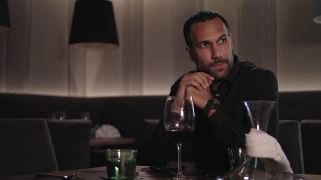 Tanned man with dark short hair and trimmed beard in classic black shirt with wrist watch is waiting for his late date girl wife to arrive, he is sitting in a hotel restaurant at a table in front of a glass of red wine and decanter.