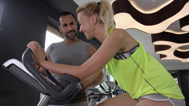 tanned personal trainer gives blonde sporty woman advice in the gym while she is exercising on a ergometer, she is cycling for fat burning and cardio training on a ergometer exercise bike