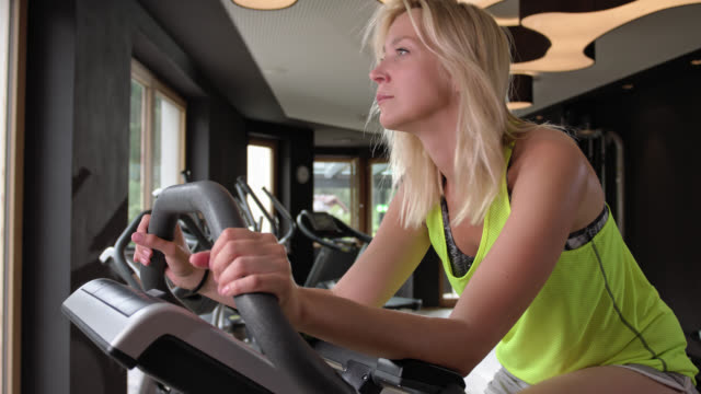 tanned personal trainer gives blonde woman advice in the gym while she is spinning on a ergometer, she is cycling for fat burning and cardio training on a ergometer exercise bike