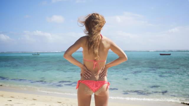 Tanned young woman in bikini at the beach