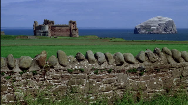 vídeos y material grabado en eventos de stock de tantallon castle on coast of firth of forth with bass rock in background and old stone fence in foreground.  east lothian, scotland - pared de piedra