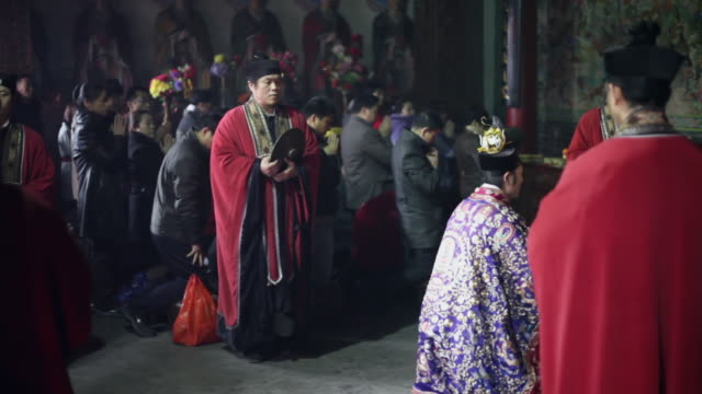 ms pan taoist do religious rites with pilgrims to pray for good luck in grand hall of temple during chinese lunar new year  audio  / xi'an, shaanxi, china - 朝聖者 個影片檔及 b 捲影像