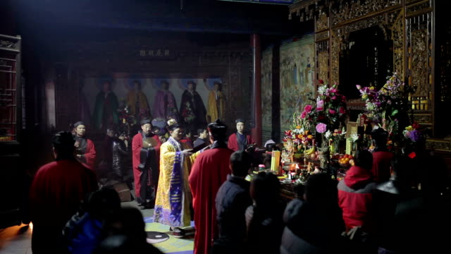 ms taoist do religious rites with pilgrims to pray for good luck in grand hall of temple during chinese lunar new year audio / xi'an, shaanxi, china - 朝聖者 個影片檔及 b 捲影像