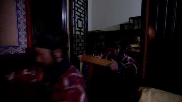 Taoist monks carry items into a monastery.