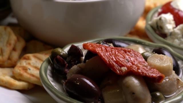 vídeos de stock, filmes e b-roll de prato de tapas com alcachofra de azeitonas recheadas de pimentão - comida salgada