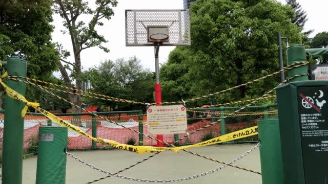 tape covers the entrance to a basketball court to prevent people playing during the continuing state of emergency because of the coronavirus pandemic... - basketball sport stock videos & royalty-free footage