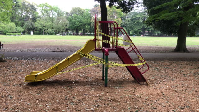 tape is placed around a slide and a climbing frame that have been closed off to protect against the spread of covid-19 coronavirus in a children's... - climbing frame stock videos & royalty-free footage