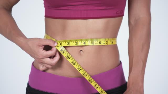 ms tape measured around woman's waist / orem, utah, usa  - orem video stock e b–roll